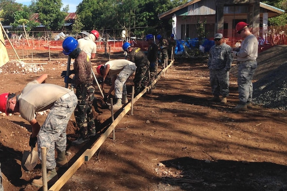Members from the 554th Red Horse Squadron and the Philippine Army's 53rd Engineer Brigade dig a continuous footer for a two-classroom building July 22, 2015, in Cebu Province, Philippines. U.S. military and Armed Forces of the Philippines members came together for a joint exchange project to construct a two-classroom school building and provide repairs at San Remigio Central Elementary School. (U.S. Air Force photo by 1st Lt. Christopher Post/Released)