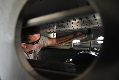 Senior Airman Jacob drives a holding pin in place on a lift cylinder on a 60K aircraft loader during maintenance at an undisclosed location in Southwest Asia May 24, 2015. The holding pin keeps the lift cylinder in place and allows it to lower and raise the aircraft loader. Jacob is a material handling equipment mechanic assigned to the Expeditionary Logistics Readiness Squadron. Due to safety and security reasons, last names and unit designators were removed. (U.S. Air Force photo/Tech. Sgt. Christopher Boitz)