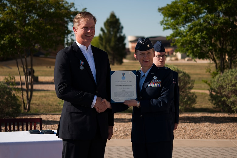 GOODFELLOW AIR FORCE BASE, Texas – Col. Kimberlee P. Joos, 17th Training Wing Commander, presents the Public Service Award to Paul Clever during a ceremony in front of the Norma Brown Building April 30. The award recognized Clever and his wife for their distinguished service in recovering human remains from a Vietnam crash site to confirm the identities of seven of the CAP-72 crewmembers who were shot down by enemy forces over southern Laos in 1969, one of whom was Clever's father. (U.S. Air Force photo/ Airman 1st Class Devin Boyer)