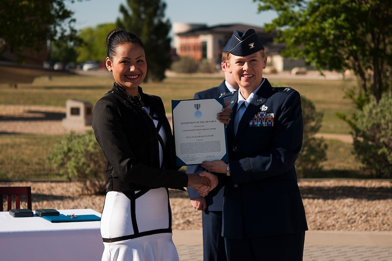 GOODFELLOW AIR FORCE BASE, Texas – Col. Kimberlee P. Joos, 17th Training Wing Commander, presents the Public Service Award to Nita Clever during a ceremony in front of the Norma Brown Building April 30. The award recognized Clever and her husband for their distinguished service in recovering human remains from a Vietnam crash site to confirm the identities of seven of the CAP-72 crewmembers who were shot down by enemy forces over southern Laos in 1969, one of whom was Clever's father-in-law. (U.S. Air Force photo/ Airman 1st Class Devin Boyer)