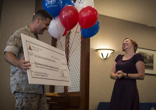 Col. Robert B. Boucher, commanding officer of MCAS Iwakuni, presents a $50,275 check to Deanna O'neal, director of the NMCRS Iwakuni, during an award ceremony inside of Talbots for unit representatives of the Active Duty Fund Drive, May 29, 2015. Donations made to the ADFD go right back into the pockets of Marines and sailors in cases of emergencies. The ADFD runs annually, March through April, by request of the Commandant of the Marine Corps and the Chief of Naval Operations and in the last four years the total amount of money donated increased every year.