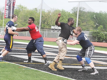 Sgt. Darrell Buckley, canvassing recruiter at Recruiting Substation Trenton, rips and swims past an offensive lineman during a drill at the Semper Fi All American Football Camp at Bridgewater-Raritan High School in Bridgewater, N.J., May 31, 2015.