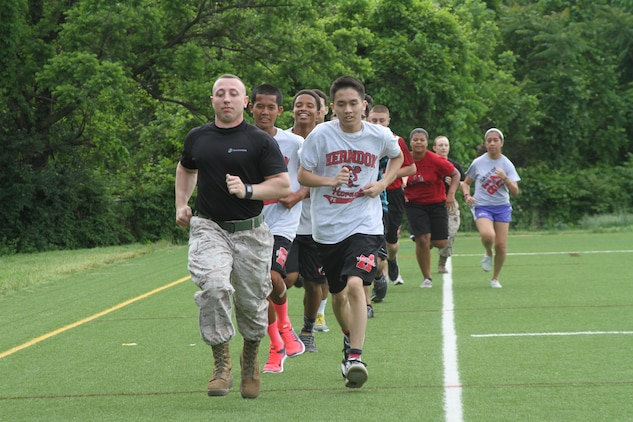 U.S. Marine Corps Sgt. Michael A. DeCamilla Jr., recruiter for Recruiting Sub-station Leesburg and native of Rochester, New York, sets the pace for Herndon High School students May 19, 2015, in Herndon, Virginia. Throughout the day, DeCamilla and other Marines multiple of students through a series of physically demanding exercises including ammunition can lifts, squad pushups and relay races. (U.S. Marine Corps photo by Sgt. Anthony Kirby/Released)
