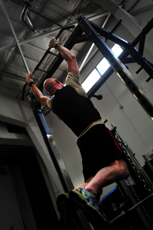 A member of the 26th Special Tactics Squadron completes pull-ups with a 25-pound vest during a physical fitness standards study, May 5, 2015, at Cannon Air Force Base, N.M. The results of this study will help the Air Force Fitness Unit develop and validate recommendations for occupationally-specific, operationally-relevant, and gender-neutral physical tests and standards. (U.S. Air Force photo/ Senior Airman Eboni Reece)