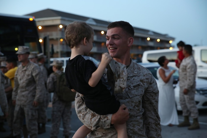 Capt. Alexander Puraty, Company B commander, Ground Combat Element Integrated Task Force, embraces his son upon return to Marine Corps Base Camp Lejeune, North Carolina, May 29, 2015. The company's Amphibious Assault Vehicle Platoon was the last of the Task Force to complete their Marine Corps Operational Test and Evaluation Activity assessment, aboard Marine Corps Base Camp Pendleton, California. From October 2014 to July 2015, the GCEITF conducted individual and collective level skills training in designated ground combat arms occupational specialties in order to facilitate the standards-based assessment of the physical performance of Marines in a simulated operating environment performing specific ground combat arms tasks. (U.S. Marine Corps photo by Cpl. Paul S. Martinez/Released)