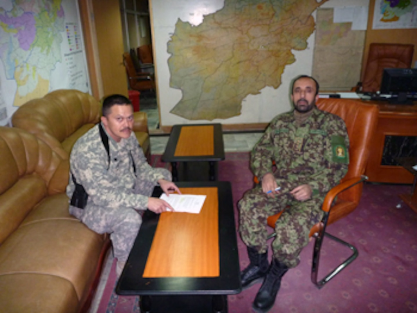 Army Lt. Col. Paul Loftus of the Virginia National Guard and Afghan Col. Qadir discuss daily operations at the NMCC Headquarters in Kabul, Afghanistan.