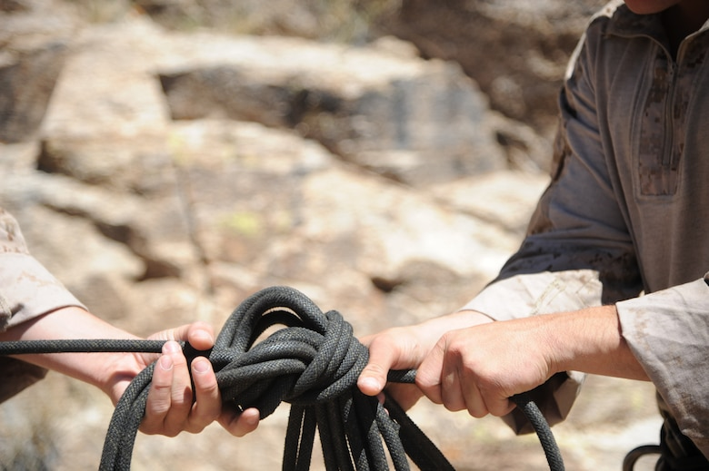 U.S. Marines Corps Cpls. Dave and Dan Peete, reconnaissance Marines, work together to tie a football knot during Angel Thunder 2015 high angle rescue training at Mount Lemmon, Ariz., June 1, 2015. During the training, U.S. Marines and U.S. Airmen practiced tying knots, anchoring ropes, rappelling down a cliffside unassisted, and returning to the initial elevation point. Angel Thunder is an Air Combat Command-sponsored personnel recovery exercise for combat air force, joint, allied and interagency participants. The Peetes' are assigned to Force Company, 1st Reconnaissance Battalion, 1st Marine Division at Camp Pendleton, Calif. (U.S. Air Force photo by Senior Airman Betty R. Chevalier/Released)