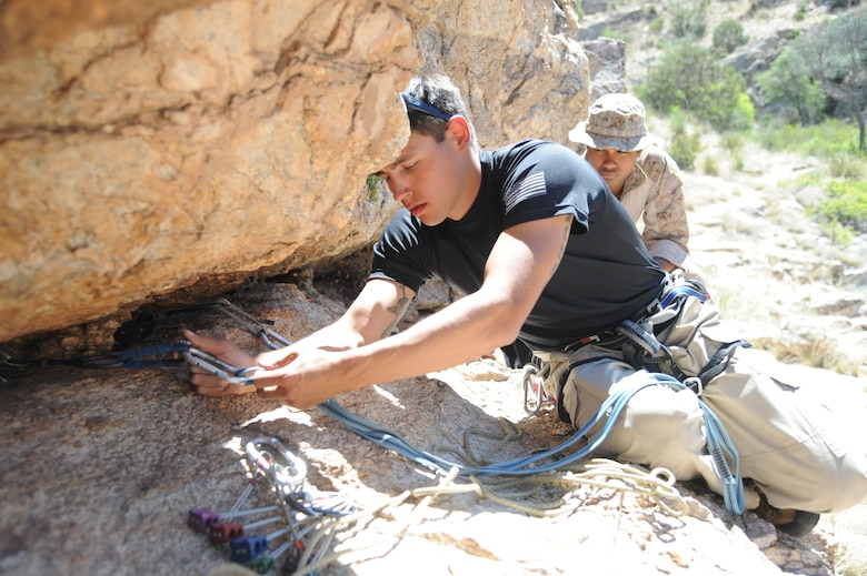 U.S. Marine Corps Sgt. Adam Martinez, Expeditionary Operations Training Group instructor, demonstrates how to use improvised rappel anchors to fellow Marines during  Angel Thunder 2015 high angle rescue training at Mount Lemmon, Ariz., June 1, 2015. During the training, U.S. Marines and U.S. Airmen practiced tying knots, anchoring ropes, rappelling down a cliffside unassisted, and returning to the initial elevation point. Angel Thunder is an Air Combat Command-sponsored personnel recovery exercise for combat air force, joint, allied and interagency participants. The Marines are assigned to Force Company, 1st Reconnaissance Battalion, 1st Marine Division at Camp Pendleton, Calif. (U.S. Air Force photo by Senior Airman Betty R. Chevalier/Released)