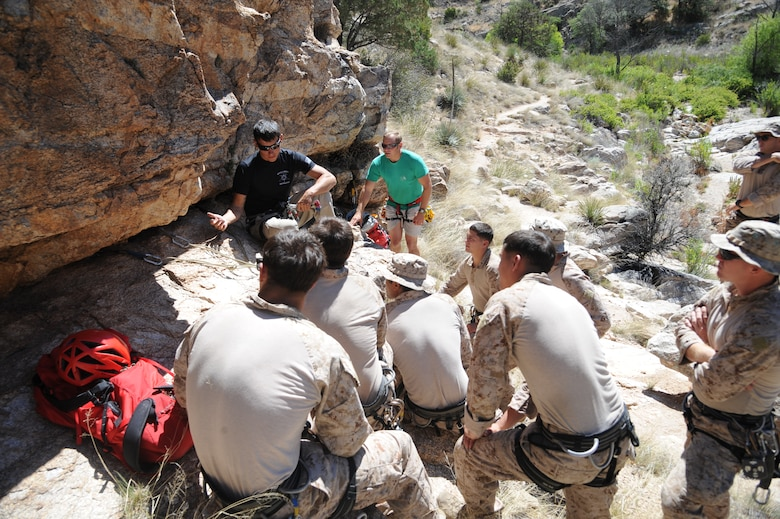 U.S. Marine Corps Sgt. Adam Martinez, Expeditionary Operations Training Group instructor, teaches a group of fellow Marines about improvised rappel anchors during Angel Thunder 2015 high angle rescue training at Mount Lemmon, Ariz., June 1, 2015. During the training, U.S. Marines and U.S. Airmen practiced tying knots, anchoring ropes, rappelling down a cliffside unassisted, and returning to the initial elevation point. Angel Thunder is an Air Combat Command-sponsored personnel recovery exercise for combat air force, joint, allied and interagency participants. The Marines are assigned to Force Company, 1st Reconnaissance Battalion, 1st Marine Division at Camp Pendleton, Calif. (U.S. Air Force photo by Senior Airman Betty R. Chevalier/Released)
