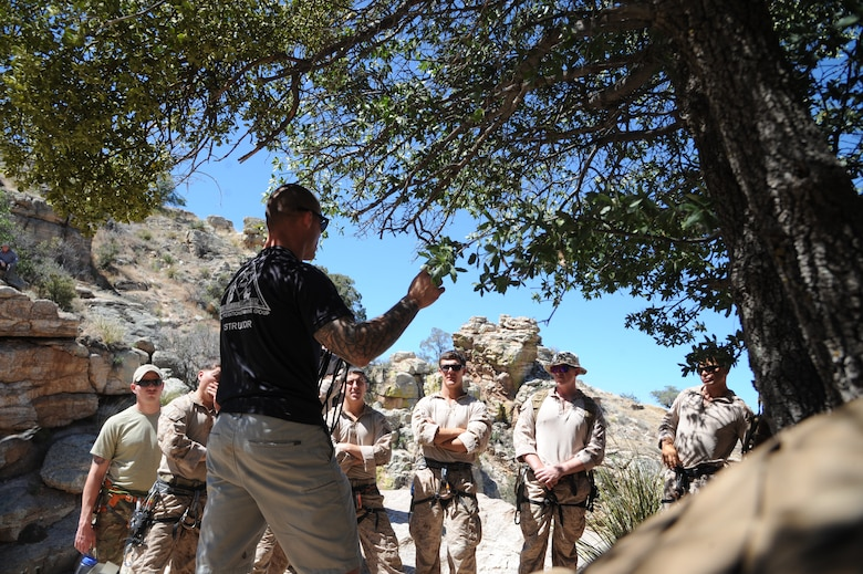 U.S. Marine Corps Staff Sgt. Adam Morrison, Expeditionary Operations Training Group instructor, speaks to fellow Marines about different ways to anchor a rappel rope using the natural environment during Angel Thunder 2015 high angle rescue training at Mount Lemmon, Ariz., June 1, 2015. During the training, U.S. Marines and U.S. Airmen practiced tying knots, anchoring ropes, rappelling down a cliffside unassisted, and returning to the initial elevation point. Angel Thunder is an Air Combat Command-sponsored personnel recovery exercise for combat air force, joint, allied and interagency participants. The Marines are assigned to Force Company, 1st Reconnaissance Battalion, 1st Marine Division at Camp Pendleton, Calif. (U.S. Air Force photo by Senior Airman Betty R. Chevalier/Released)