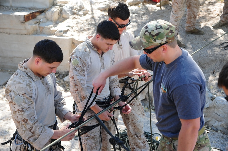 U.S. Air Force Senior Airman Miles Roberts, reserve pararescueman, assists U.S. Marine Corps Cpl. Dan Peete, reconnaissance Marine, tie a knot designed to stay secure while rappelling during Angel Thunder 2015 high angle rescue training at Mount Lemmon, Ariz., June 1, 2015. During the training, U.S. Marines and U.S. Airmen practiced tying knots, anchoring ropes, rappelling down a cliffside unassisted, and returning to the initial elevation point. Angel Thunder is an Air Combat Command-sponsored personnel recovery exercise for combat air force, joint, allied and interagency participants. Roberts is assigned to the 304th Rescue Squadron at Portland Air National Guard Base, Ore., and Peete is assigned to Force Company, 1st Reconnaissance Battalion, 1st Marine Division at Camp Pendleton, Calif. (U.S. Air Force photo by Senior Airman Betty R. Chevalier/Released)
