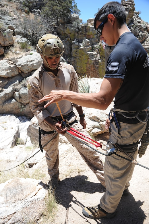 U.S. Marine Sgt. Adam Martinez, Expeditionary Operations Training Group instructor, teaches U.S. Navy Hospital Corpsman 3rd Class Chris Trinidad, special amphibious reconnaissance corpsman , how to make a unassisted hand brake during Angel Thunder 2015 high angle rescue training at Mount Lemmon, Ariz., June 1, 2015. During the training, U.S. Marines and U.S. Airmen practiced tying knots, anchoring ropes properly, rappelling down a cliffside unassisted, and returning to the initial elevation point. Martinez is assigned to the Expeditionary Operations Training Group and Trinidad is assigned to Force Company, 1st Reconnaissance Battalion, 1st Marine Division both at Camp Pendleton, Calif. (U.S. Air Force photo by Tech. Sgt. Courtney Richardson/Released)