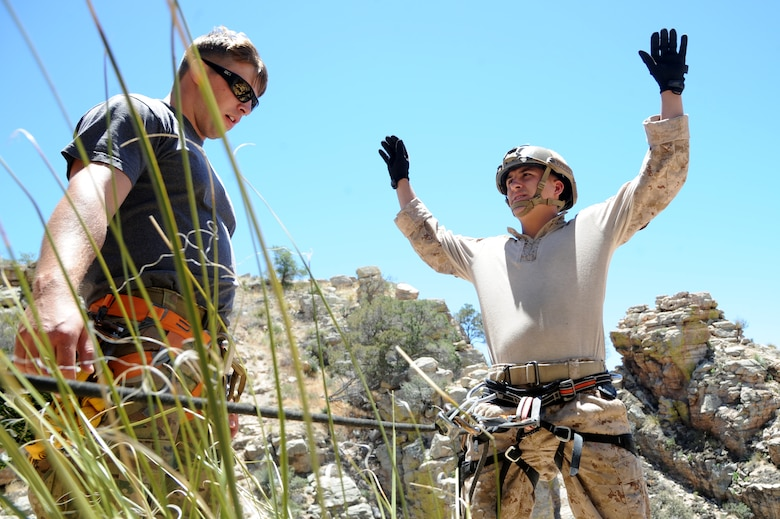 U.S. Air Force Senior Airman Miles Roberts, 304th Rescue Squadron pararescueman, watches the rope as U.S. Marine Corporal Dan Peete, reconnaissance Marine, makes sure his harness is properly secured to the anchored rope duringAngel Thunder 2015 high angle rescue training at Mount Lemmon, Ariz., June 1, 2015. During the training, U.S. Marines and U.S. Airmen practiced tying knots, anchoring ropes properly, rappelling down a cliffside unassisted, and returning to the initial elevation point. Roberts is assigned to the 304th Rescue Squadron is stationed at Portland Air National Guard Base, Ore. and Peete is assigned to Force Company, 1st Reconnaissance Battalion, 1st Marine Division at Camp Pendleton, Calif. (U.S. Air Force photo by Tech. Sgt. Courtney Richardson/Released)