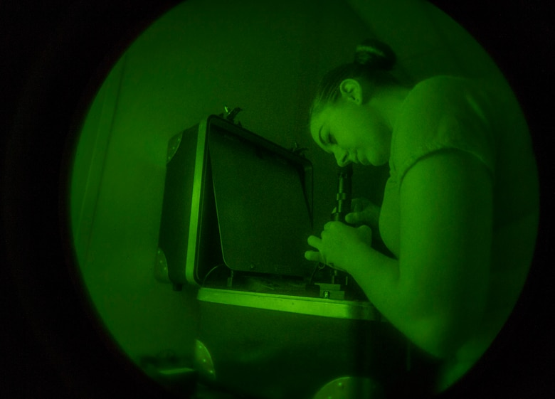 Airman 1st Class Lacey McGee, 811th Operations Support Squadron aircrew flight equipment technician, tests night vision goggles on Joint Base Andrews, Md., May 26, 2015. This 180-day inspection ensures they are operable and free from spots in the field of view. (U.S. Air Force photo/Airman 1st Class Ryan J. Sonnier)
