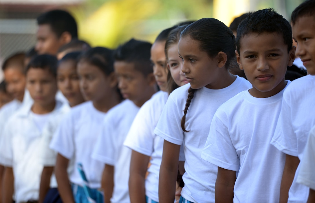Gabirela Mistral students watch the groundbreaking ceremony at the Gabriela Mistral school in Ocotoes Alto, Honduras, June 1, 2015. The children performed a number of dance routines as part of the ceremony which also marked the first day of the New Horizons Honduras 2015 training exercise taking place in and around the Trujillo and Tocoa areas. New Horizons was launched in the 1980s and is an annual joint humanitarian assistance exercise that U.S. Southern Command conducts with a partner nation in Central America, South America or the Caribbean. The exercise improves joint training readiness of U.S. and partner nation civil engineers, medical professionals and support personnel through humanitarian assistance activities. (U.S. Air Force photo by Capt. David J. Murphy/Released)