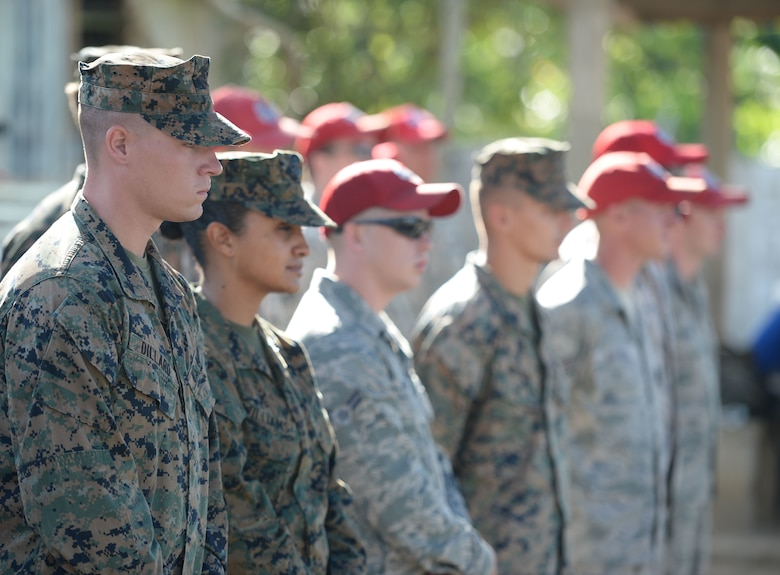 U.S. Air Force Airmen from the 823rd Expeditionary RED HORSE Squadron, out of Hurlburt Field, Fla., and U.S. Marines from the 271st Marine Wing Support Squadron, 2nd Marine Air Wing, out of Marine Corps Air Station Cherry Point, N.C., watch the groundbreaking ceremony at the Gabriela Mistral school in Ocotoes Alto, Honduras, June 1, 2015. The Airmen and Marines will be working together as part of the New Horizons Honduras 2015 training exercise, an annual humanitarian exercise put on by U.S. Southern Command. New Horizons was launched in the 1980s and is an annual joint humanitarian assistance exercise that U.S. Southern Command conducts with a partner nation in Central America, South America or the Caribbean. The exercise improves joint training readiness of U.S. and partner nation civil engineers, medical professionals and support personnel through humanitarian assistance activities. (U.S. Air Force photo by Capt. David J. Murphy/Released)