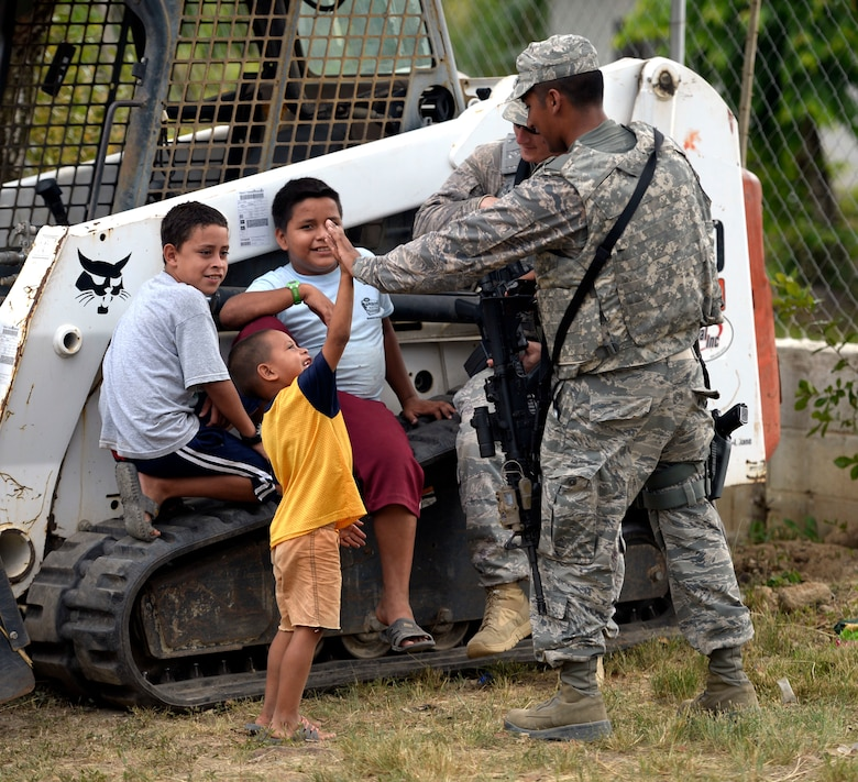 U.S. Air Force Senior Airman Pedro Zambrano, a Dallas, Texas, native with the 301st Security Forces Squadron, out of Carswell, Texas, high fives Christian Trochez, 4, at the Gabriela Mistral primary school construction site in Ocotoes Alto, Honduras, June 1, 2015. Tech. Sgt. Erik Barber, a Arlington, Texas, native with the 610th Security Forces Squadron, also out of Carswell, Texas, hangs out with Osman (center), 13, and Denniz Trochez (left), 10, his cousins. Zambrano and Barber are responsible for security inside the construction site supporting the New Horizons Honduras 2015 training exercise. New Horizons was launched in the 1980s and is an annual joint humanitarian assistance exercise that U.S. Southern Command conducts with a partner nation in Central America, South America or the Caribbean. The exercise improves joint training readiness of U.S. and partner nation civil engineers, medical professionals and support personnel through humanitarian assistance activities. (U.S. Air Force photo by Capt. David J. Murphy/Released)