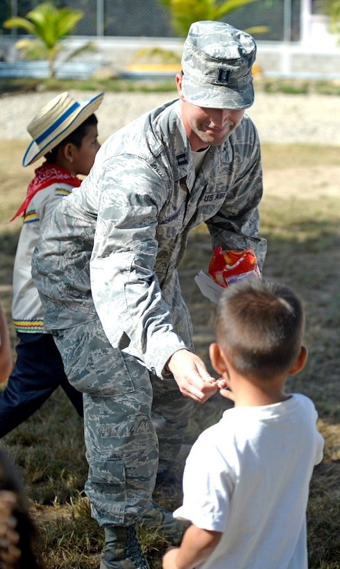 U.S. Air Force Capt. Austin McKinney, 8th Air Force Life Cycle Management Center deputy program manager out of Hanscom Air Force Base, Mass., and Canton, Mich. native, hands out candy to children following a groundbreaking ceremony at the Gabriela Mistral primary school in Ocotoes Alto, Honduras, June 1, 2015. McKinney provided translation services during the ceremony which signified the official start of the New Horizons Honduras 2015 training exercise. New Horizons was launched in the 1980s and is an annual joint humanitarian assistance exercise that U.S. Southern Command conducts with a partner nation in Central America, South America or the Caribbean. The exercise improves joint training readiness of U.S. and partner nation civil engineers, medical professionals and support personnel through humanitarian assistance activities. (U.S. Air Force photo by Capt. David J. Murphy/Released)