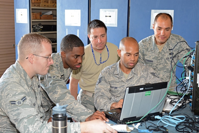 """U.S. Air Force Staff Sgt. Darius Carter and Airman Tyler Kulig with the help from others in the 290th Joint Communications Support Squadron """"B-Flight"""" troubleshoot the setup and configuration of a JBlox baseband equipment at MacDill Air Force Base, Tampa Florida, May 3, 2015. The JBlox baseband equipment is used to connect phones and computers to satellite systems. (U.S. Air Force photo by SSgt Troy Anderson/Released)"""