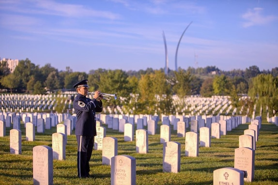 Chief Master Sgt Robert McConnell, a member of the Ceremonial Brass, renders TAPS at Arlington National Cemetery, with the Air Force Memorial visible in the background. 