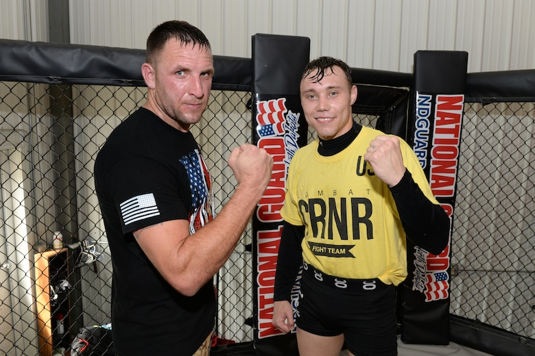 Senior Airman Michael Bullen, right, and Tech. Sgt. Gemenie Strehlow, both of the 119th Security Forces Squadron pose for a photo in the mixed martial arts cage at a Fargo, North Dakota, gym, May 8, 2015. The Airmen are training at the gym to enhance their fitness and skills to be better prepared in their career field for potential threats on duty. Bullen is scheduled for a competitive mixed martial arts match May 16 in Detroit Lakes, Minnesota. (U.S. Air National Guard photo by Senior Master Sgt. David H. Lipp/Released)
