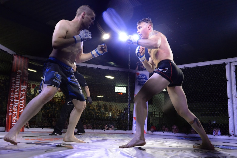 Senior Airman Michael Bullen, of the 119th Security Forces Squadron, right, faces off with his opponent during his mixed martial arts fight in the center stage fighting cage at the Freeman Arena, Detroit Lakes, Minnesota, May 16, 2015. The security forces Airman uses mixed martial arts training and fighting to enhance his fitness and skills to be better prepared in his career field and to be better prepared for potential threats on duty.  (U.S. Air National Guard photo by Senior Master Sgt. David H. Lipp/Released)