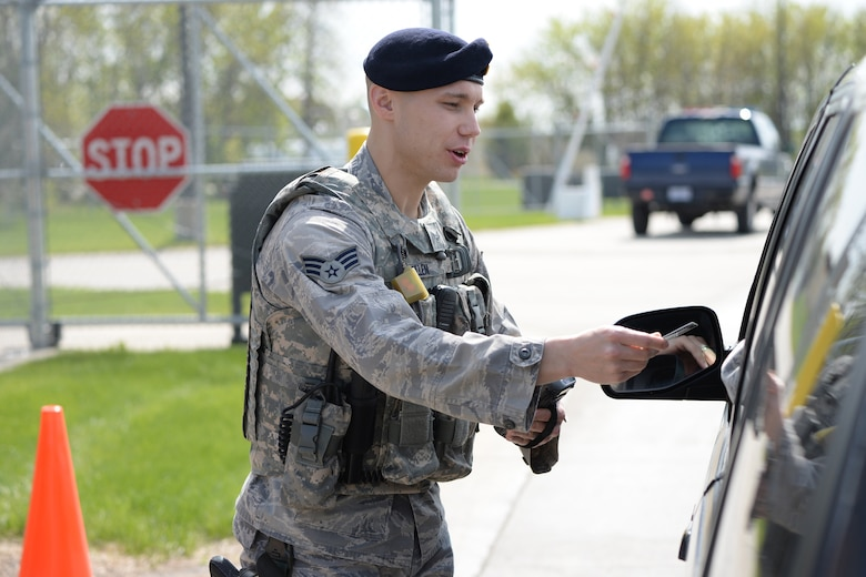Senior Airman Michael Bullen, of the 119th Security Forces Squadron, checks the identification of personnel entering the North Dakota Air National Guard Base, Fargo, North Dakota, May 12, 2015. (U.S. Air National Guard photo by Senior Master Sgt. David H. Lipp/Released)