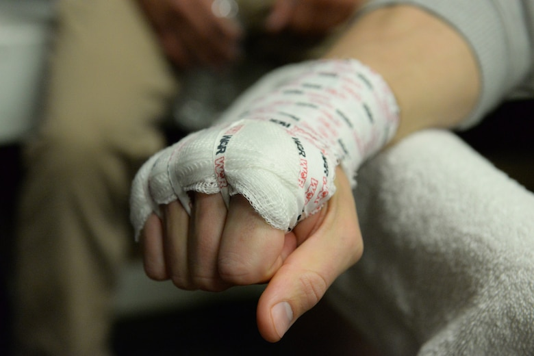 Senior Airman Michael Bullen, of the 119th Security Forces Squadron, makes a fist after his hand is wrapped prior to putting on his fighting gloves, as he prepares for a mixed martial arts fight May 16, 2015, the Freeman Arena, Detroit Lakes, Minnesota. The security forces Airman uses mixed martial arts training and fighting to enhance his fitness and skills to be better prepared in his career field and to be better prepared for potential threats on duty.  (U.S. Air National Guard photo by Senior Master Sgt. David H. Lipp/Released)