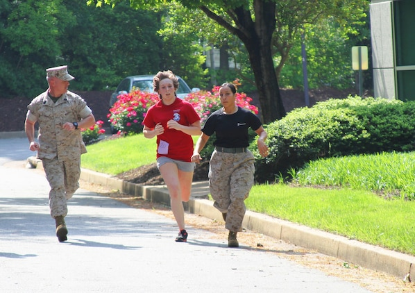 A female member  of Marine Corps Recruiting Station Richmond's delayed entry program is motivated during the run portion of the initial strength test by Sgt. Maj. David Eldridge, Recruiting Station Richmond's sergeant major, and Cpl. Kansas Ledezma, Recruiting Station Richmond's administration clerk, and a native of Buckhannon, West Virginia, during the station's annual female pool function. The event gave the female poolees an opportunity to learn what they can expect aboard Marine Corps Recruit Depot Parris Island, as they undergo the longest and most difficult boot camp within the U.S. armed services to earn the coveted title of United States Marine.
