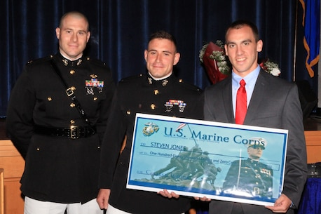 Steven Jones, a resident of Tolland, Connecticut, and recent graduate of Tolland High School, is one of this year's Naval Reserve Officer Training Corps Scholarship Program, Marine Corps Option, recipients. Maj. Thomas Abbott, left, and 1st Lt. Stefan Milan, center, present Jones with a $180,000 scholarship during a high school awards ceremony June 2, 2014, at the school. (Official U.S. Marine Corps photo by Staff Sgt. Richard Blumenstein.)