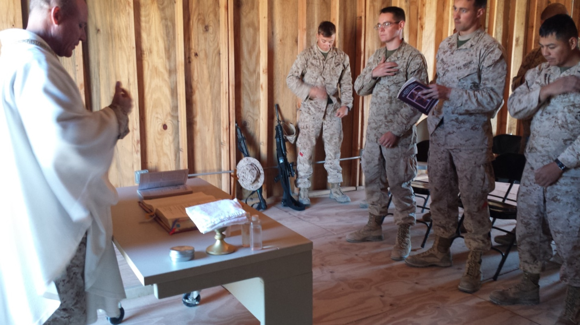LFT to RT: Chaplain David Daigle, LCpl Brownlee, LCpl Hurla, LCpl Brady, 1st Lt Heriberto Lopez Father Daigle reading the Word of the Lord.  Building Spiritual Resiliency:  One of the great challenges of meeting the mission is being ready at all times. Desert FIREX 2015 happened to span the Holy Week for Christians of all denominations. One of the various ways the Navy Chaplain Corps helps to ensure Marines and Sailors are growing in their faith is through field worships services.  Attending Easter Protestant Field Service during DESERTFIREX.  Service was provided by Chaplain Slaughter. Chaplain Slaughter provided nightly devotionals throughout the field operation. However, Easter Sunday is a special day in the eyes of many Marines and Sailors. For many this was a time to celebrate their faith. For some it was a time to rekindle their relationship with the divine. In this picture, some of the 15 attendees to the Protestant Service are gathering.