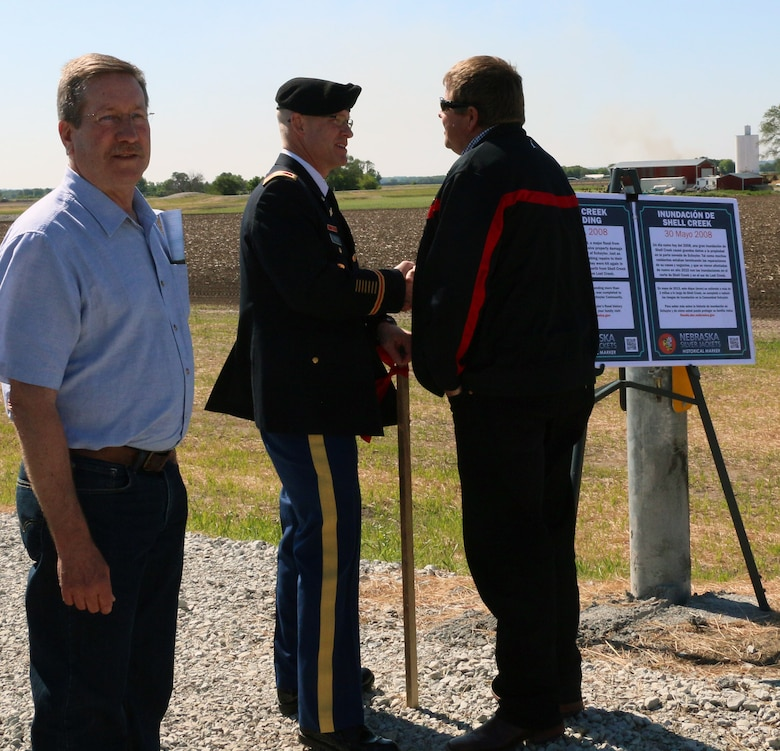 City of Schuyler Mayor David Reinecke basks in the glory of his city's new levee, while USACE Omaha District Commander Col. Joel Cross shakes hands with Mike Murren from the Lower Platte North Natural Resources District.