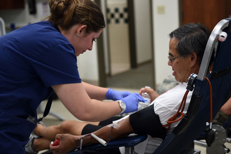 Sarah Adams, Bonfils Blood Bank phlebotomist, prepares to take Tony Chan's blood during the blood drive June 2, 2015, at the Health and Wellness Center on Buckley Air Force Base, Colo. The blood drive was to support hospitals in the local area. (U.S. Air Force photo by Airman 1st Class Emily E. Amyotte/Released)