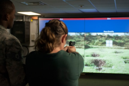U.S. Air Force Tech. Sgt. Franklin Mosley, 633rd Security Forces Squadron, instructs Dina Persico, Kecoughtan High School teacher, on proper shooting procedures using a range simulator at Langley Air Force Base, Va., May 29, 2015. Persico and more than 100 students from Hampton Roads area high schools toured Langley to learn about the Air Force mission and the installation Airman's impact. (U.S. Air Force photo by Senior Airman R. Alex Durbin/Released)