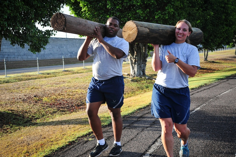 "Capt. Jerrel Scriven, Joint Task Force-Bravo director of protocol, and Capt. Laura Miller, JTF-B adjutant, carry logs around the track at Soto Cano Air Base, Honduras, June 03, 2015. This is one of many exercises in the grueling workout known as ""Sgt. Maj. PT,"" a training session led JTF-B's Command Sgt. Maj., Nelson Callahan, that encourages members to ""lead by example, to break a sweat, to blast [their] core and to build unit cohesion"" (U.S. Air Force photo by Capt. Christopher Love)."