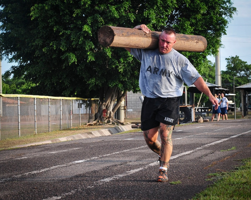 "Command Sgt. Maj. Nelson Callahan, Joint Task Force-Bravo Command Sgt. Maj., carries a log around the track at Soto Cano Air Base, Honduras, June 03, 2015. During his year at Soto Cano, CSM Callahan has used his famous ""Sgt. Maj. PT"" sessions to strengthen JTF-B physically and as a team (U.S. Air Force photo by Capt. Christopher Love)."
