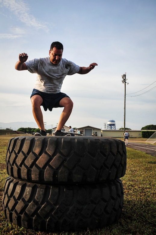 "Lt. Col. Mathew Contreras, Joint Task Force-Bravo deputy commanding officer, jumps onto a stack of tires during a specialized physical training session June 03, 2015, at Soto Cano Air Base, Honduras. Known as ""Sgt. Maj. PT,"" these workouts, led by Command Sgt. Maj. Nelson Callahan, JTF-B Command Sgt. Maj., afford service members the chance to strengthen themselves physically and as a team (U.S. Air Force photo by Capt. Christopher Love)."
