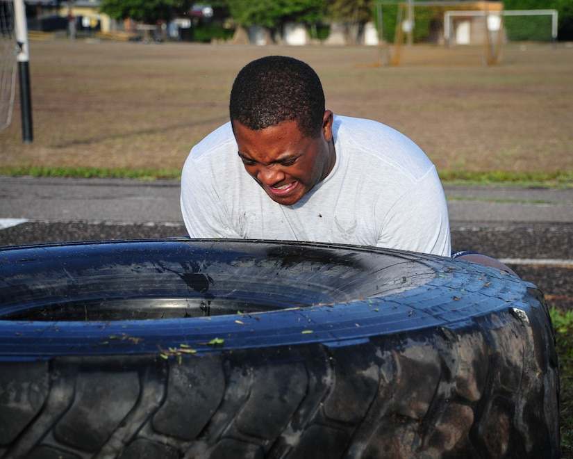 "Capt. Jerrel Scriven, Joint Task Force-Bravo director of protocol, braces to flip a tire during a ""Sgt. Maj. PT"" session June 03, 2015, at Soto Cano Air Base, Honduras. These sessions, led by Command Sgt. Maj. Nelson Callahan, JFT-B Command Sgt. Maj., afford service members the chance to strengthen themselves physically and as a team."