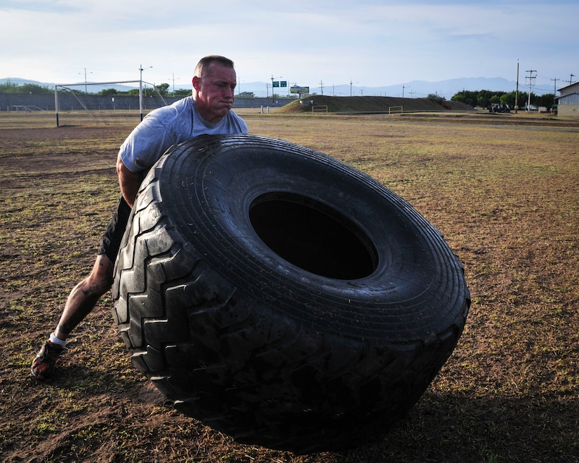 "Command Sgt. Maj. Nelson Callahan, Joint Task Force-Bravo Command Sgt. Maj., flips a tire as part of a physical training session June 03, 2015, at Soto Cano Air Base, Honduras. A dedicated athlete and mentor, CSM Callahan invites others to join him during this specialized physical training session so they can ""lead by example…break a sweat…blast [their] core and…build unit cohesion"" (U.S. Air Force photo by Capt. Christopher Love)."