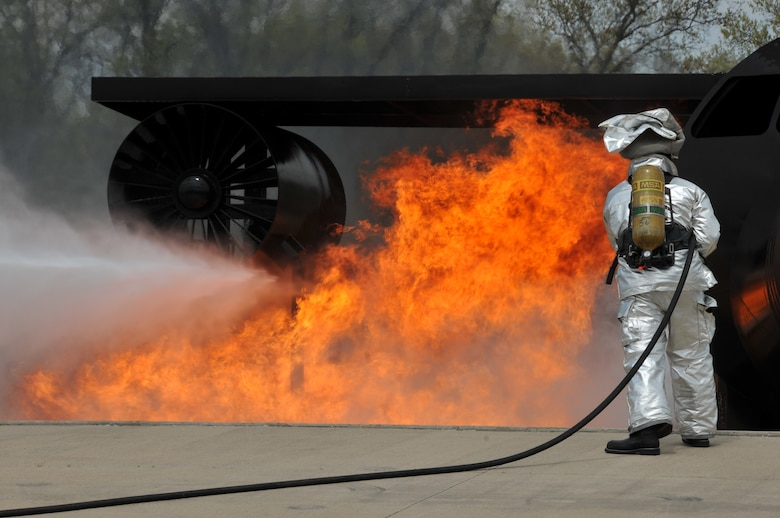 A firefighter from the 114th Civil Engineer Squadron puts out a simulated aircraft engine burn as part of their live fire training at Volk Field, Wisc. May 6, 2015. The firefighters travel to Volk Field each year to hone their basic skills and to train on a simulated burning aircraft. (National Guard photo by Senior Airman Duane Duimstra/Released)