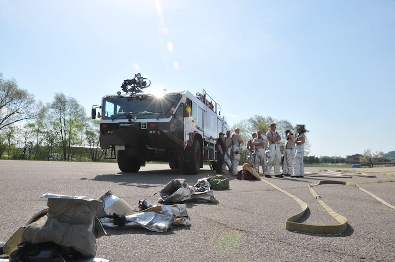 Firefighters from the 114th Civil Engineer Squadron discuss the next exercise during their training at Volk Field, Wisc. May 6, 2015. The firefighters travel to Volk Field each year to hone their basic skills and to train on a simulated burning aircraft. (National Guard photo by Senior Airman Duane Duimstra/Released)