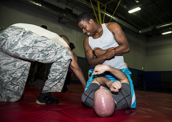 Staff Sgt. Jared Kimbrough, 379th Expeditionary Security Forces Check Six facilitator and training non-commissioned officer in charge, instructs Senior Airmen Dustin Kepley and Geon Butler, how to defend themselves, while in the non-dominant position during a combatives class at the Blanchard-Preston Complex gym May 29, 2015 at Al Udeid Air Base, Qatar. Both Airmen are attached to 379th Expeditionary Communications Squadron. Bi-weekly, members of the 379th Expeditionary Security Forces Squadron members instruct members on non-lethal ways to defend themselves. (U.S. Air Force photo/Tech. Sgt. Rasheen Douglas)