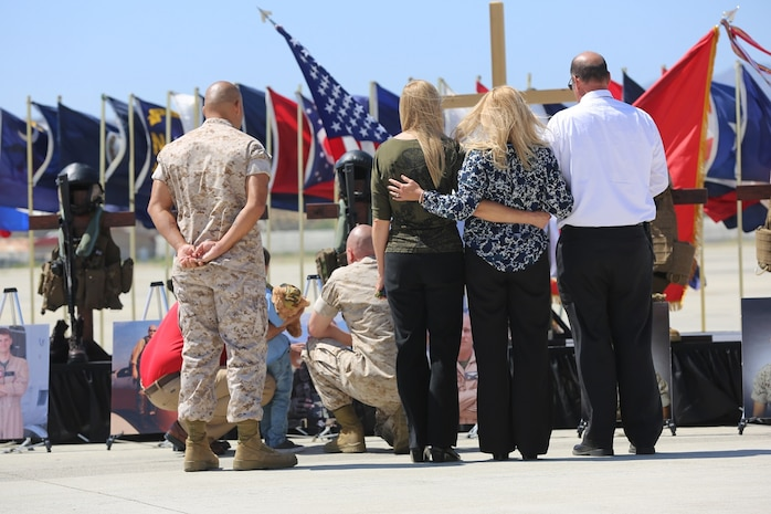 Family and friends gather in front of a display dedicated to fallen Marines at a memorial service aboard Marine Corps Air Station Camp Pendleton, California, June 3. The ceremony honored six Marines killed in a UH-1Y helicopter crash while conducting relief efforts in Nepal.