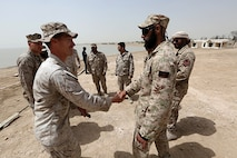 Staff Sgt. Jimmy Arbuthnot, an explosive ordnance disposal technician with Combat Logistics Battalion 24, 24th Marine Expeditionary Unit, shakes hands with a Kuwaiti EOD technician during Exercise Eagle Resolve 2015 at Failaka Island, Kuwait, March 23, 2015. Eagle Resolve is the premiere Arabian Peninsula/gulf region exercise among the United States, Gulf Cooperation Council nations, and international partners. It serves to address regional challenges associated with asymmetric/unconventional warfare in a multi-national environment. (U.S. Marine Corps photo by Sgt. Devin Nichols)