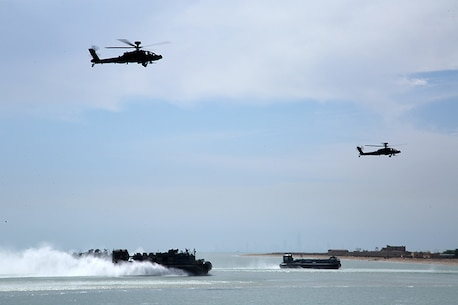 A U.S. Navy Landing Craft, Air Cushion vessel attached to the Iwo Jima Amphibious Ready Group and a Kuwaiti hovercraft approach the beach while being escorted by a pair of Kuwaiti Apache helicopters during an simulated amphibious assault as a part of Exercise Eagle Resolve 2015 at Failaka Island, Kuwait, March 24, 2015. Eagle Resolve is the premiere Arabian Peninsula/gulf region exercise among the United States, Gulf Cooperation Council nations, and international partners. It serves to address regional challenges associated with asymmetric/unconventional warfare in a multi-national environment. (U.S. Marine Corps photo by Sgt. Devin Nichols)