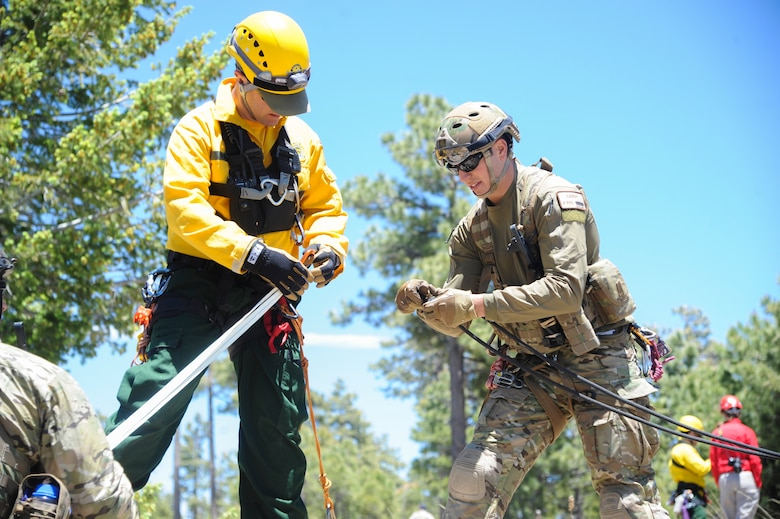 John Vonk, Grand Canyon National Park Service search and rescue team member, and U.S. Air Force Staff Sgt. Matthew Gaddy, 306th Rescue Squadron reserve pararescueman, connect ropes to pull a simulated patient to the top of a steep cliffside during Angel Thunder 2015 high angle rescue training at Mongollon Rim, Ariz., June 3, 2015. Angel Thunder is hosted by the 355th Fighter Wing at Davis-Monthan Air Force Base, Ariz., but many flying operation will extend throughout Arizona, New Mexico and California. (U.S. Air Force photo by Senior Airman Betty R. Chevalier/Released)