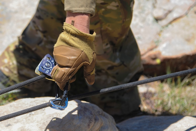 A 306th Rescue Squadron reserve pararescueman resets a pulley system used to pull a simulated patient over a steep cliffside during Angel Thunder 2015 high angle rescue training at Mongollon Rim, Ariz., June 3, 2015. Angel Thunder is the world's largest personnel recovery exercise, hosting 11 partner nations and nine interagencies at Davis-Monthan Air Force Base, Ariz. (U.S. Air Force photo by Senior Airman Betty R. Chevalier/Released)