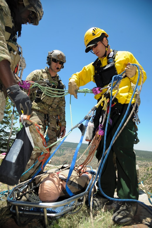 John Vonk, Grand Canyon National Park Service search and rescue team member, verifies rescue equipment is assembled properly to a 306th Rescue Squadron reserve pararescueman and a gurney before lowering them over a cliffside during Angel Thunder 2015 high angle rescue training at Mongollon Rim, Ariz., June 3, 2015. The objective of the exercise is to train personnel recovery forces to prepare, plan, execute and adapt for a rescue mission. (U.S. Air Force photo by Senior Airman Betty R. Chevalier/Released)