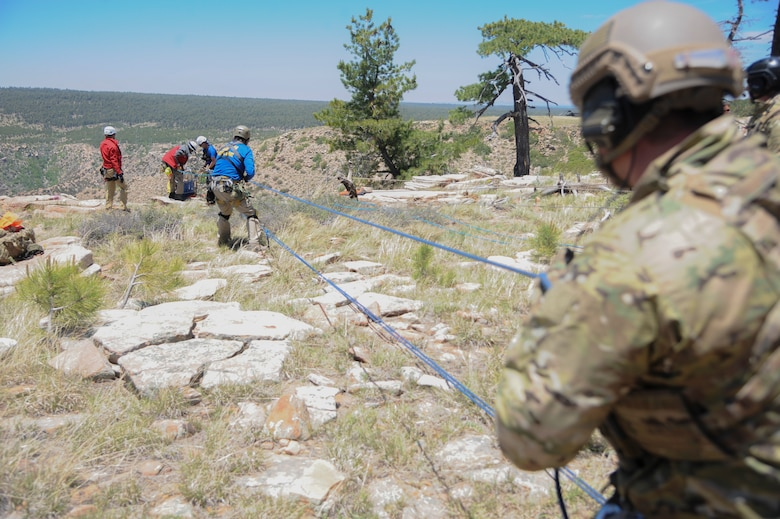 A 306th Rescue Squadron reserve pararescueman and members of several interagency search and rescue teams use combined strength to hoist a simulated patient up a steep cliffside during Angel Thunder 2015 high angle rescue training at Mongollon Rim, Ariz., June 3, 2015. Angel Thunder is hosted by the 355th Fighter Wing at Davis-Monthan Air Force Base, Ariz., but many flying operation will extend throughout Arizona, New Mexico and California. (U.S. Air Force photo by Senior Airman Betty R. Chevalier/Released)