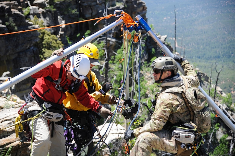 Members of several interagency search and rescue teams and a 306th Rescue Squadron reserve pararescueman connect ropes to an Arizona Vortex Tripod during Angel Thunder 2015 high angle rescue training at Mongollon Rim, Ariz., June 3, 2015. The objective of the exercise is to train personnel recovery forces to prepare, plan, execute and adapt for a rescue mission. (U.S. Air Force photo by Senior Airman Betty R. Chevalier/Released)
